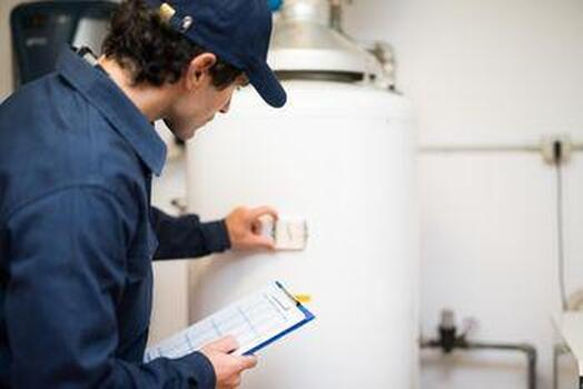 Picture of a licensed plumber inspecting a water heater tank